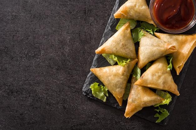 Samsa ou samosas avec viande et légumes sur fond noir. fond Photo Premium