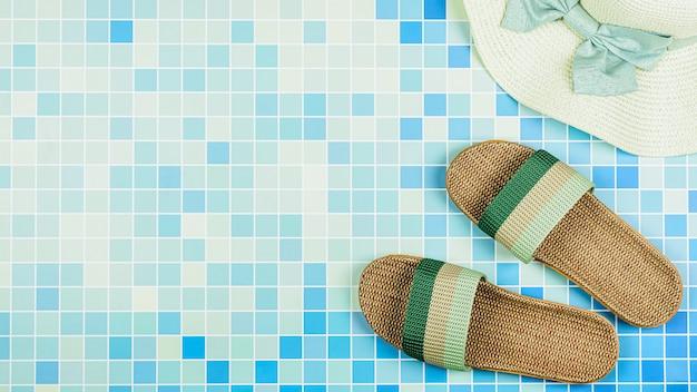 Sandales et un chapeau de plage sur des carreaux de céramique bleus à la piscine. Photo Premium