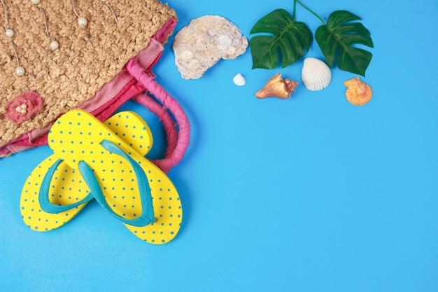 Sandales jaunes avec sacs à main tissés sur fond de couleur bleue Photo Premium