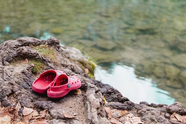Sandales En Plastique Rose Femme Sur Un Rocher Près D'un Lac Photo Premium
