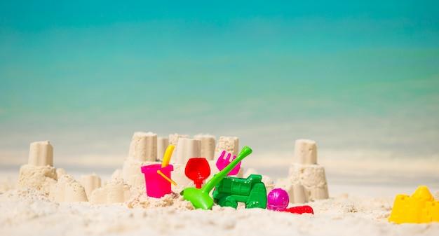 Sandcastle à la plage blanche avec des jouets en plastique Photo Premium