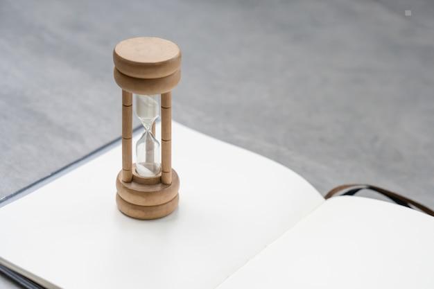 Sandglass gisait sur le livre blanc propre Photo Premium