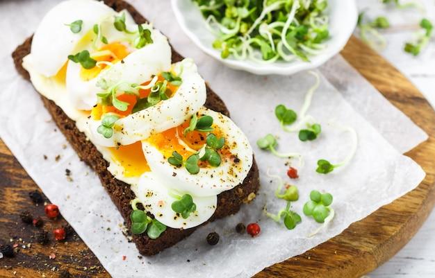 Sandwich au pain de seigle avec œuf à la coque, fromage, poivre fraîchement moulu et germes de daikon ou de radis, Photo Premium
