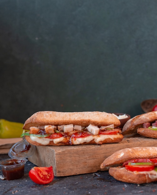 Sandwich au poulet avec des cubes de fromage feta dans du pain baguette sur une planche de bois Photo gratuit