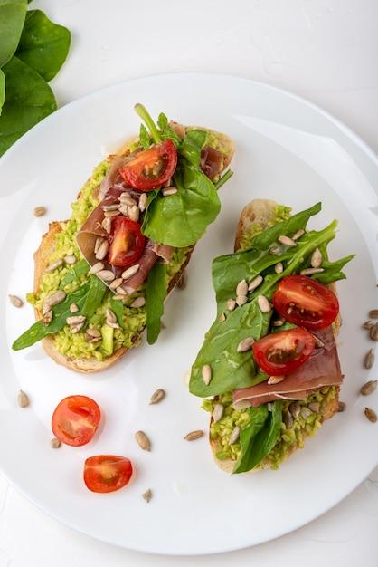 Sandwich Au Prosciutto, Jambon, Tomates Et Avocat Photo Premium