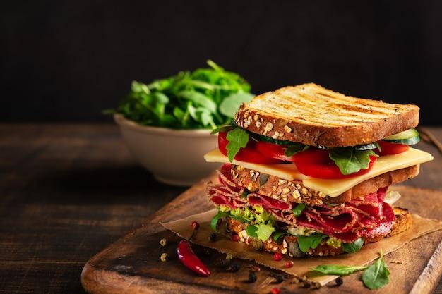Sandwich au salami, fromage et légumes frais sur une planche à découper en bois rustique Photo Premium