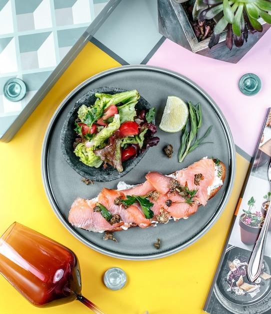Sandwich au saumon et légumes dans l'assiette Photo gratuit