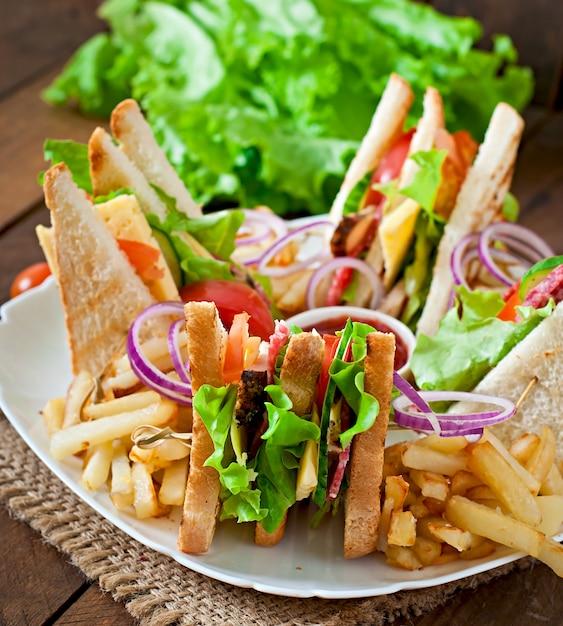 Sandwich Club Au Fromage, Concombre, Tomate, Viande Fumée Et Salami. Servi Avec Frites. Photo gratuit