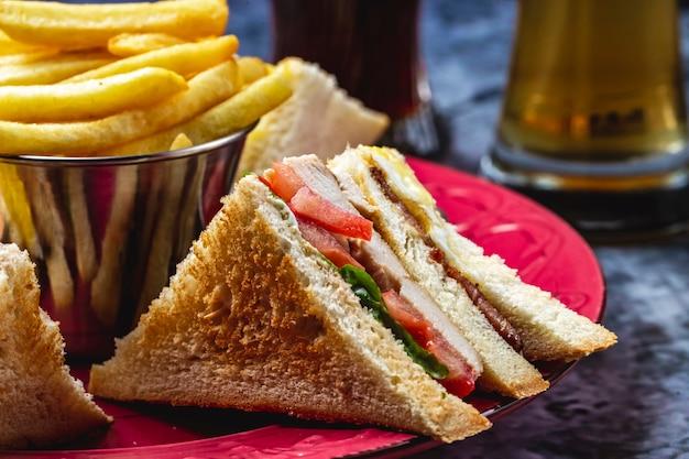 Sandwich Club Vue Latérale Avec Laitue De Poulet Grillée Et Frites Sur La Table Photo gratuit