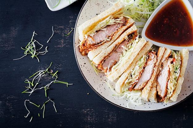 Sandwich Japonais Avec Côtelette De Porc Panée, Chou Et Sauce Tonkatsu. Photo gratuit