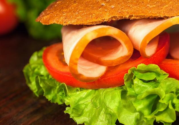 Sandwich avec laitue, tomates, jambon, sur une table en bois. fermer Photo Premium