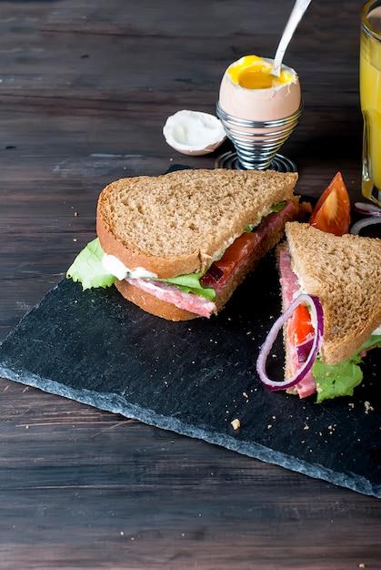 Sandwich, oeuf, tasse de café et verre de jus au petit déjeuner Photo Premium