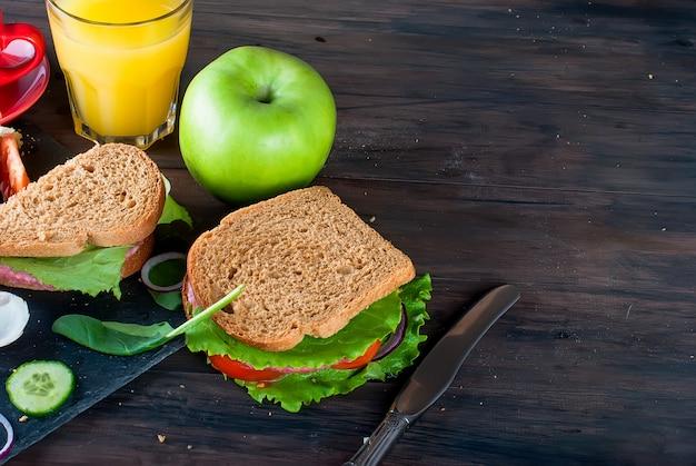 Sandwich, œuf, tasse de café et verre de jus au petit déjeuner Photo Premium