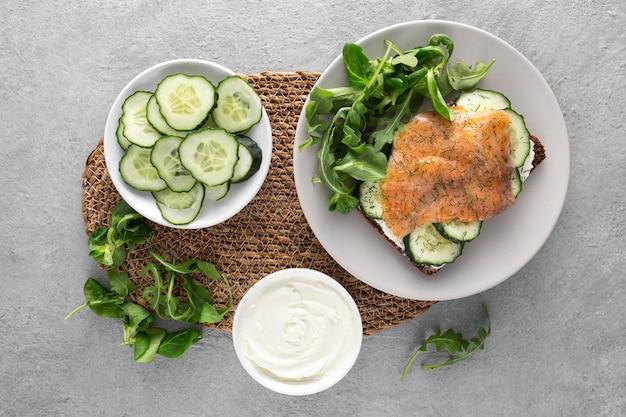 Sandwich à Plat Avec Concombres Et Saumon Sur Assiette Avec épinards Photo gratuit