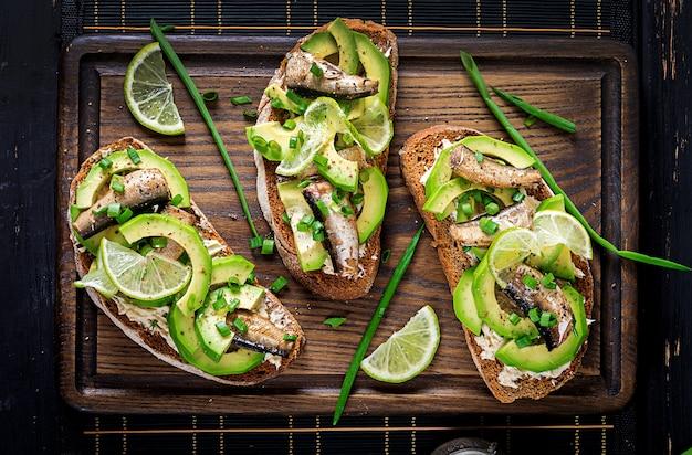Sandwich - Smorrebrod Avec Sprats, Avocat Et Fromage à La Crème Sur Planche De Bois. Cuisine Danoise. Vue De Dessus Photo Premium