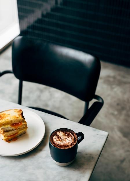 Sandwich et une tasse de café sur une table Photo gratuit
