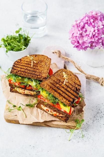 Sandwich végétalien avec tofu, houmous, avocat, tomate et choux. Photo Premium
