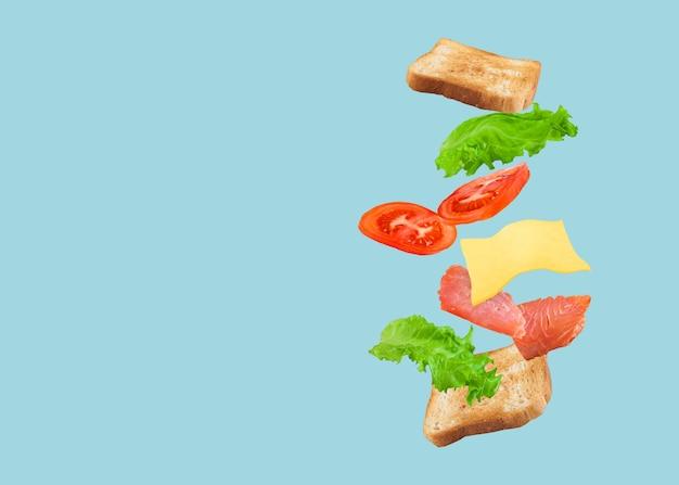 Sandwich Volant Au Saumon, Fromage Et Tomates Sur Fond Bleu. Photo Premium