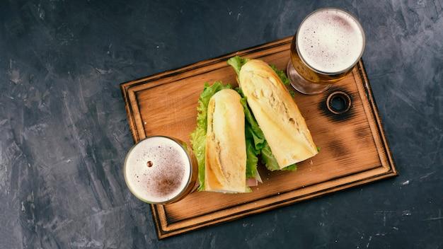 Sandwiches Au Bacon Et Au Fromage Et à La Bière Sur Une Table Sombre. Vue De Dessus. Photo Premium