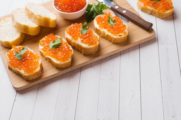 Sandwiches au caviar de saumon rouge sur une planche de bois Photo Premium