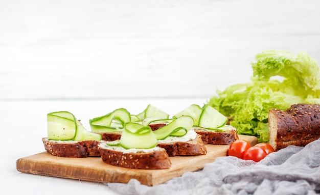 Sandwiches au fromage et au concombre. laitue et tomates cerises Photo Premium