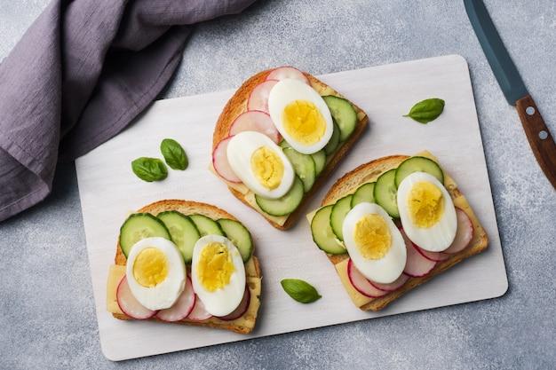 Sandwiches au fromage d'oeuf, concombre frais et radis. Photo Premium