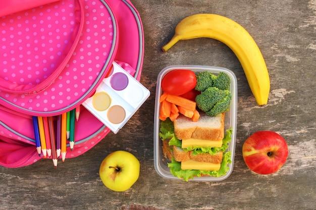 Sandwiches, Fruits Et Légumes Dans Une Boîte à Provisions, Un Sac à Dos Photo Premium