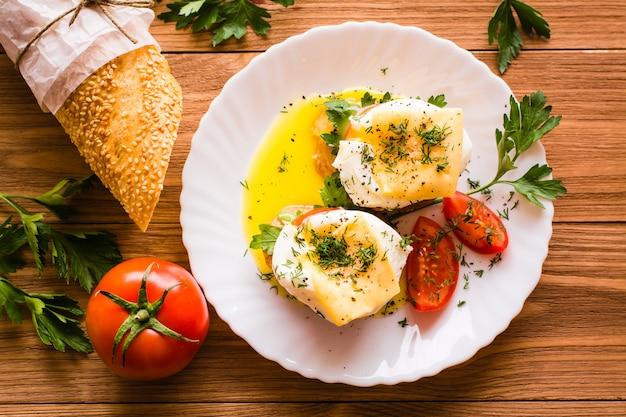 Sandwiches à l'œuf poché, à la tomate, au persil et au fromage. vue de dessus Photo Premium