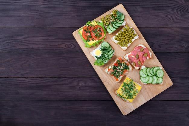 Sandwiches Sur Pain Grillé Avec Du Fromage à La Crème Avec Du Saumon, Des Germes, Des Légumes Se Trouvent Sur Une Planche De Bois Photo Premium