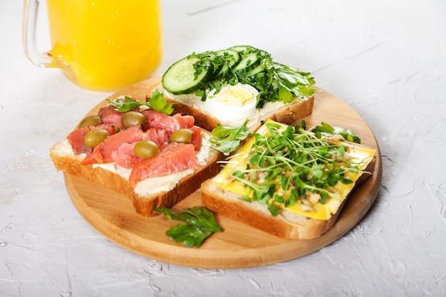 Sandwiches Sur Pain Grillé Avec Saumon, œuf, Herbes Et Légumes Sur Une Planche De Bois Et Jus D'orange Photo Premium