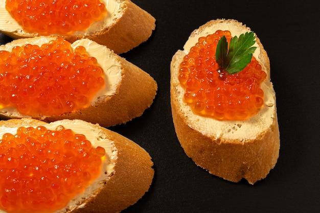 Sandwichs Au Caviar De Saumon Rouge Sur Fond De Pierre Sombre. Photo Premium