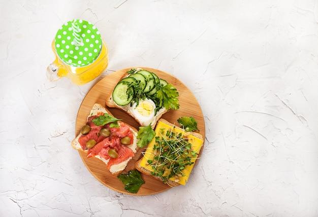 Sandwichs Au Saumon, Pousses, Tomates, Concombres, œufs Et Persil Sur Une Planche De Bois Photo Premium