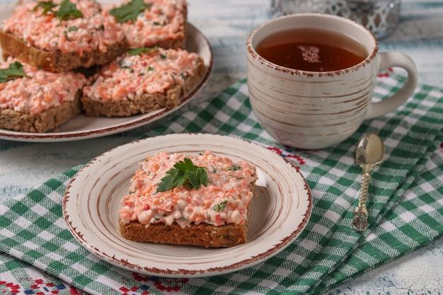 Sandwichs Faits Maison Avec Des Bâtonnets De Crabe, Du Fromage Et Des Carottes Sur Une Plaque Sur Une Nappe à Carreaux, Orientation Horizontale Photo Premium