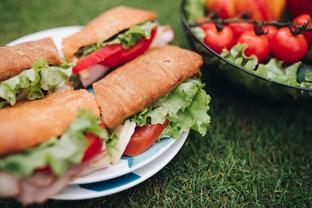 Sandwichs avec tomates, oignons et laitue restant sur plaque Photo Premium