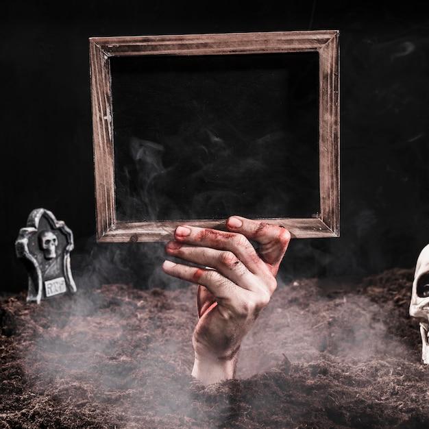Sanglante main tenant un signe noir vide Photo gratuit