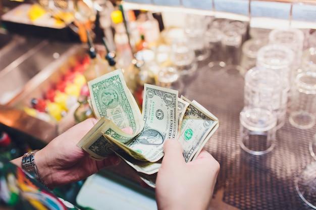 Un Sans-abri Tient Un Billet En Dollars Dans Sa Main. Mise Au Point Sélective à La Facture En Dollars. Photo Premium