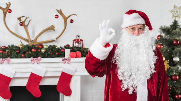 Santa montrant bon geste près de la cheminée Photo gratuit