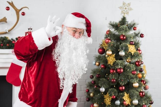 Santa montrant bon geste près de sapin de noël Photo gratuit