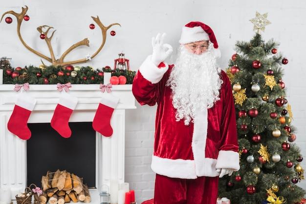Santa montrant un geste correct près de la cheminée décorée Photo gratuit
