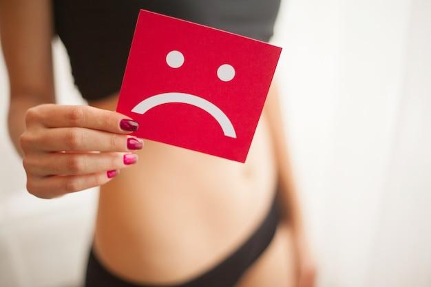 Santé de la femme. corps féminin tenant une carte de sourire triste près de l'estomac Photo Premium