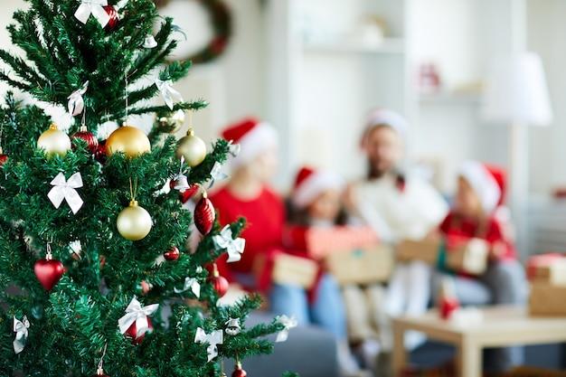 Sapin De Noël Décoré Avec Famille Floue Photo gratuit
