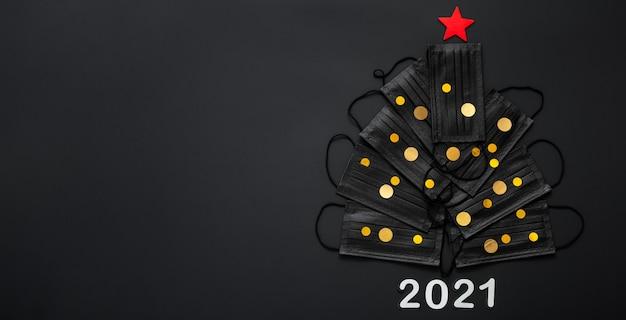 Sapin De Noël Fabriqué à Partir De Masques Faciaux Et De Confettis Décor Festif Or. Espace Copie Du Réveillon Du Nouvel An 2021. Photo Premium