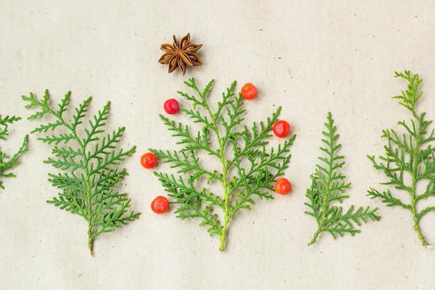 Sapin de noël fait de branches de thuya et de décorations étoiles d'anis et de framboise sur fond rustique. Photo Premium