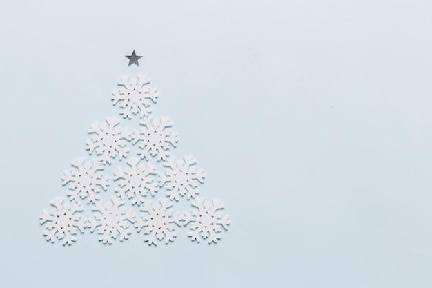 Sapin de noël fait de petits flocons de neige Photo gratuit