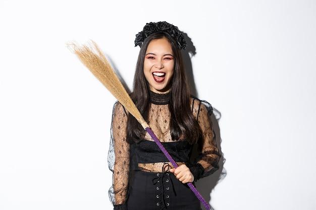 Sassy Méchante Sorcière Riant Et Agitant Son Balai, Vêtue D'un Costume D'halloween Photo gratuit
