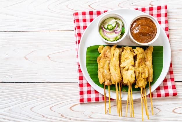 Satay De Porc - Porc Grillé Servi Avec Une Sauce Aux Arachides Ou Une Sauce Aigre-douce Photo Premium