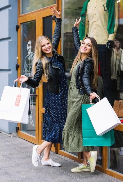 Satisfaits jeunes femmes tenant des sacs posant devant un magasin de vêtements Photo gratuit