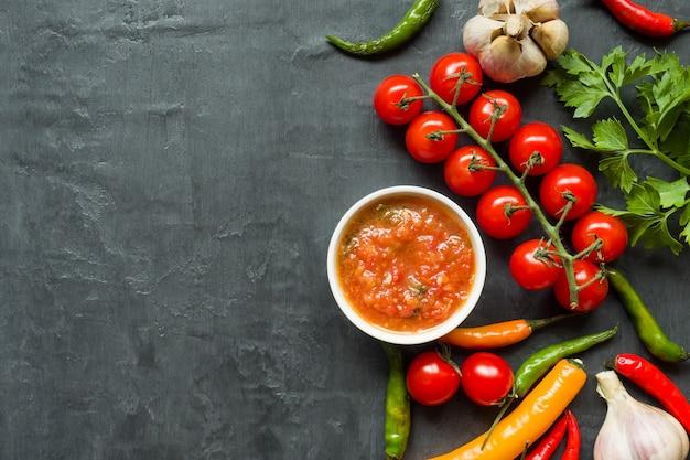 Sauce, ketchup, lecho en assiette. tomates chili, ail et autres épices sur fond noir Photo Premium