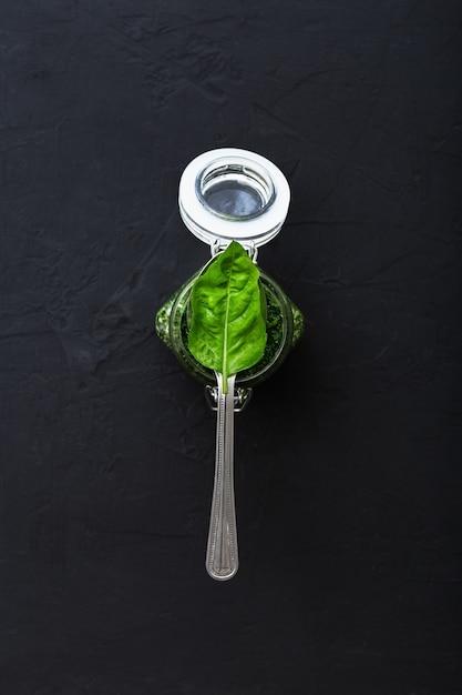 Sauce Pesto Maison Et Feuille De Basilic Vert En Cuillère Sur Fond De Ciment Foncé. Photo Premium