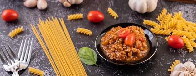 Sauce Pour Faire Sauter Des Spaghettis Ou Des Macaronis Sautés Sur Une Assiette Noire. Photo gratuit